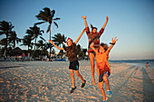 Portrait carefree family jumping on tropical beach