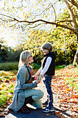 Mother and son holding hands and talking in autumn park