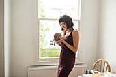 Mother holding newborn baby son at window