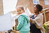 Girl helping pregnant mother hang laundry on clothesline