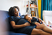 Girl leaning on pregnant mother stomach on sofa