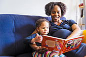 Pregnant mother reading book to daughter on sofa