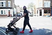 Father pushing toddler son in stroller on urban street
