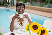 Woman drinking coffee at poolside