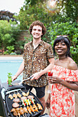 Portrait happy multiethnic couple barbecuing at poolside