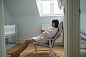 Serene pregnant woman in bathrobe relaxing in baby nursery