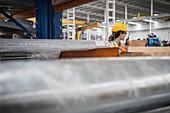 Female worker at laptop talking on walkie-talkie in factory