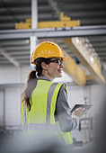Confident female worker using digital tablet in factory