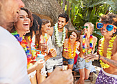 Young friends wearing leis, hanging out at summer poolside