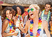 Friends wearing leis drinking and partying at sunny poolside