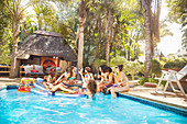 Young friends hanging out at tropical summer swimming pool