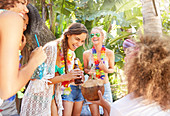 Young women friends laughing and drinking at summer party