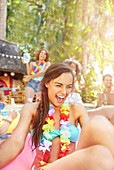 Laughing young woman wearing lei in summer swimming pool