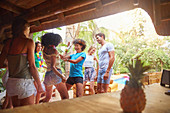 Young friends dancing out at tropical summer poolside