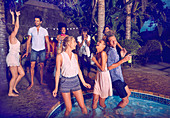 Friends hanging out at summer poolside party at night