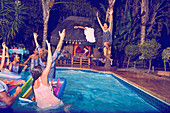Young friends playing, jumping into swimming pool at night