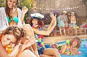 Man spraying women friends at summer swimming pool