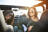 Smiling young women wearing sunglasses in sunny jeep