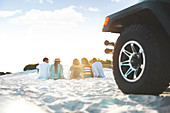 Young friends relaxing, hanging out on beach behind jeep