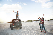 Young man on jeep tire taking selfie with friends on beach