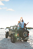 Friends cheering with arms raised in jeep on beach