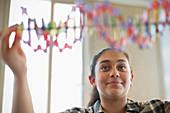 Girl student examining DNA model in classroom