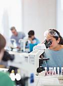 Student using microscop conducting scientific experiment