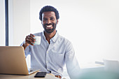 Smiling, confident businessman drinking coffee at laptop