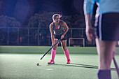 Female hockey player hitting the ball with hockey stick