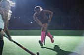 Female hockey player running with hockey stick