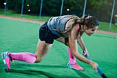 Female hockey player reaching with hockey stick