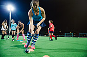 Female hockey player practicing sports drill on field