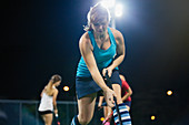 Young female field hockey player practicing sports drill