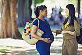Woman greeting pregnant friend in park