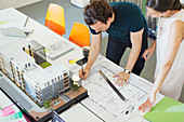 Architects drafting blueprint in office