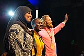 Smiling speakers waving on stage