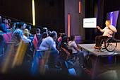 Audience listening to female speaker in wheelchair on stage
