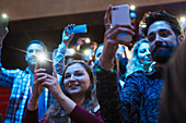 Smiling audience using smart phone flashlights