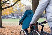 Senior woman bike riding among autumn leaves in park