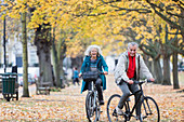 Senior couple bike riding among trees and leaves in autumn