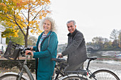 Smiling senior couple bike riding along autumn river
