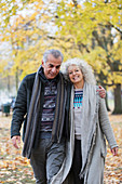 Smiling senior couple hugging and walking in autumn park