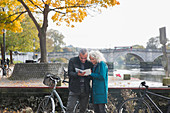 Senior couple with bicycles looking at guidebook