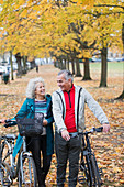 Senior couple walking bicycles among trees in autumn