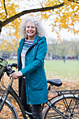Confident senior woman bike riding in autumn park
