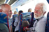 Smiling, confident active senior men tourist on tour bus