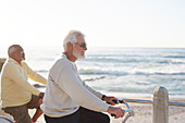 Active senior men bike riding, enjoying ocean view