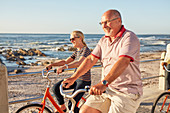 Smiling active senior tourists bike riding along sunny ocean