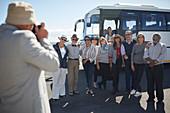 Senior tourist friends posing for photograph outside bus