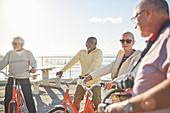 Active senior friend tourists bike riding on sunny boardwalk